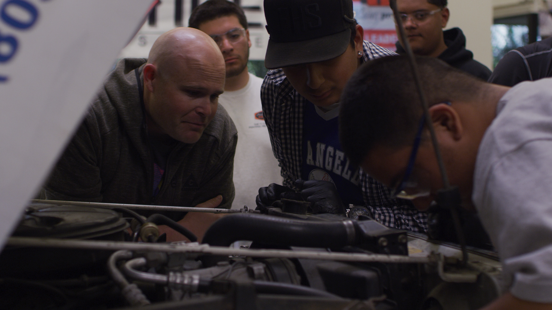 DRAGG students looking under the hood of a car.